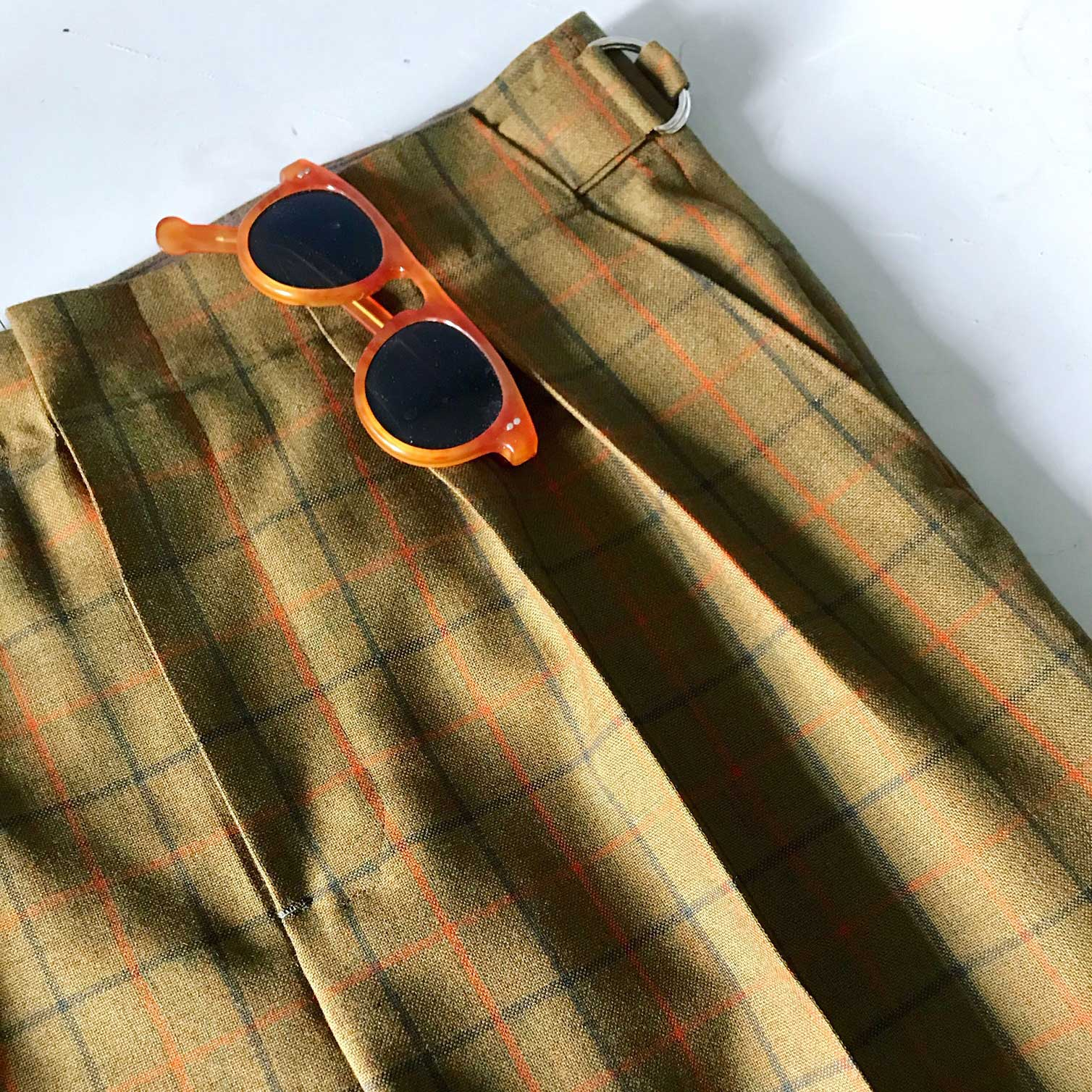 green and orange check trousers and sunglasses