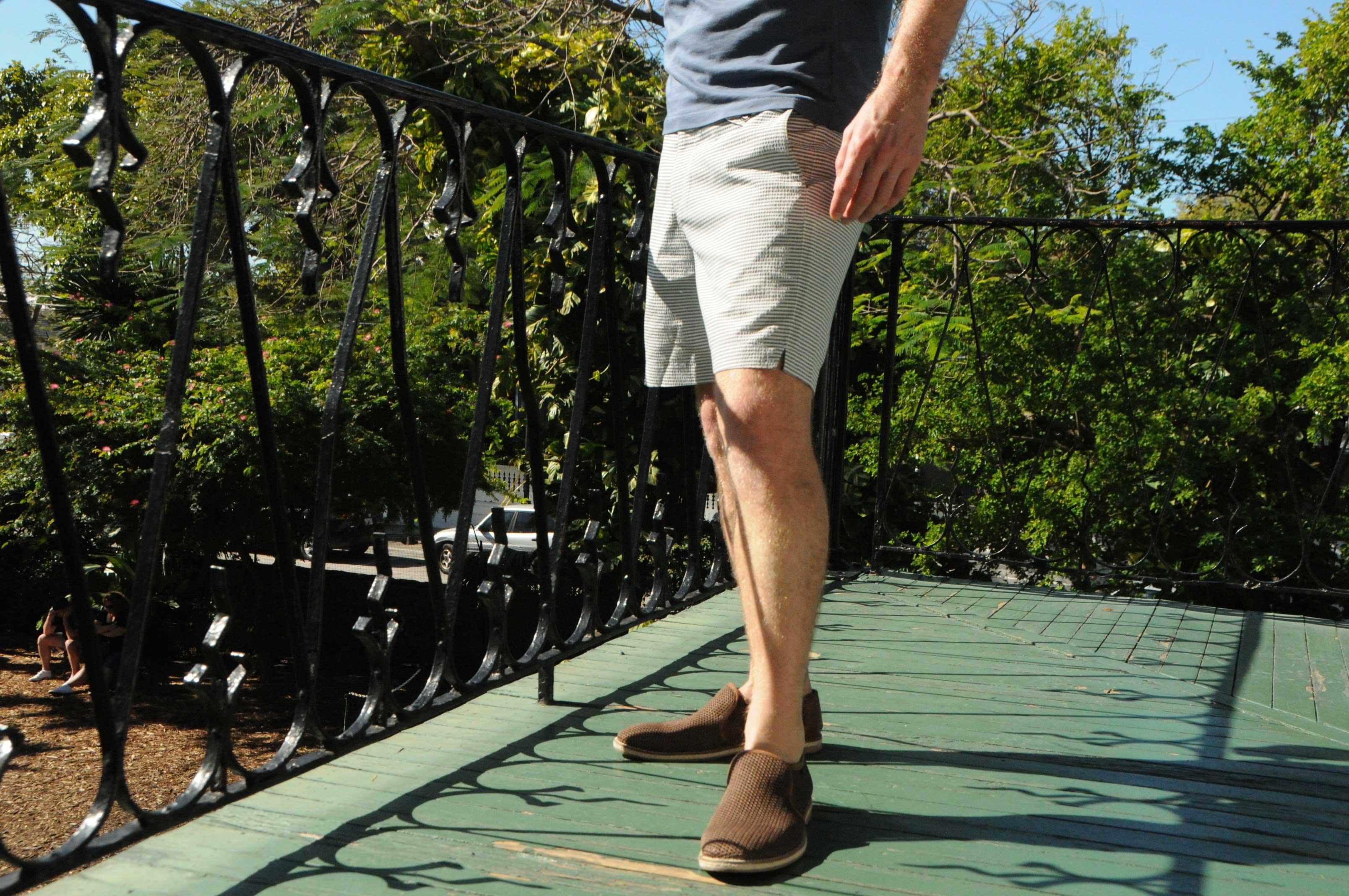 man standing on balcony hemingway house wearing Hemingsworth seerseucker and brown loafers