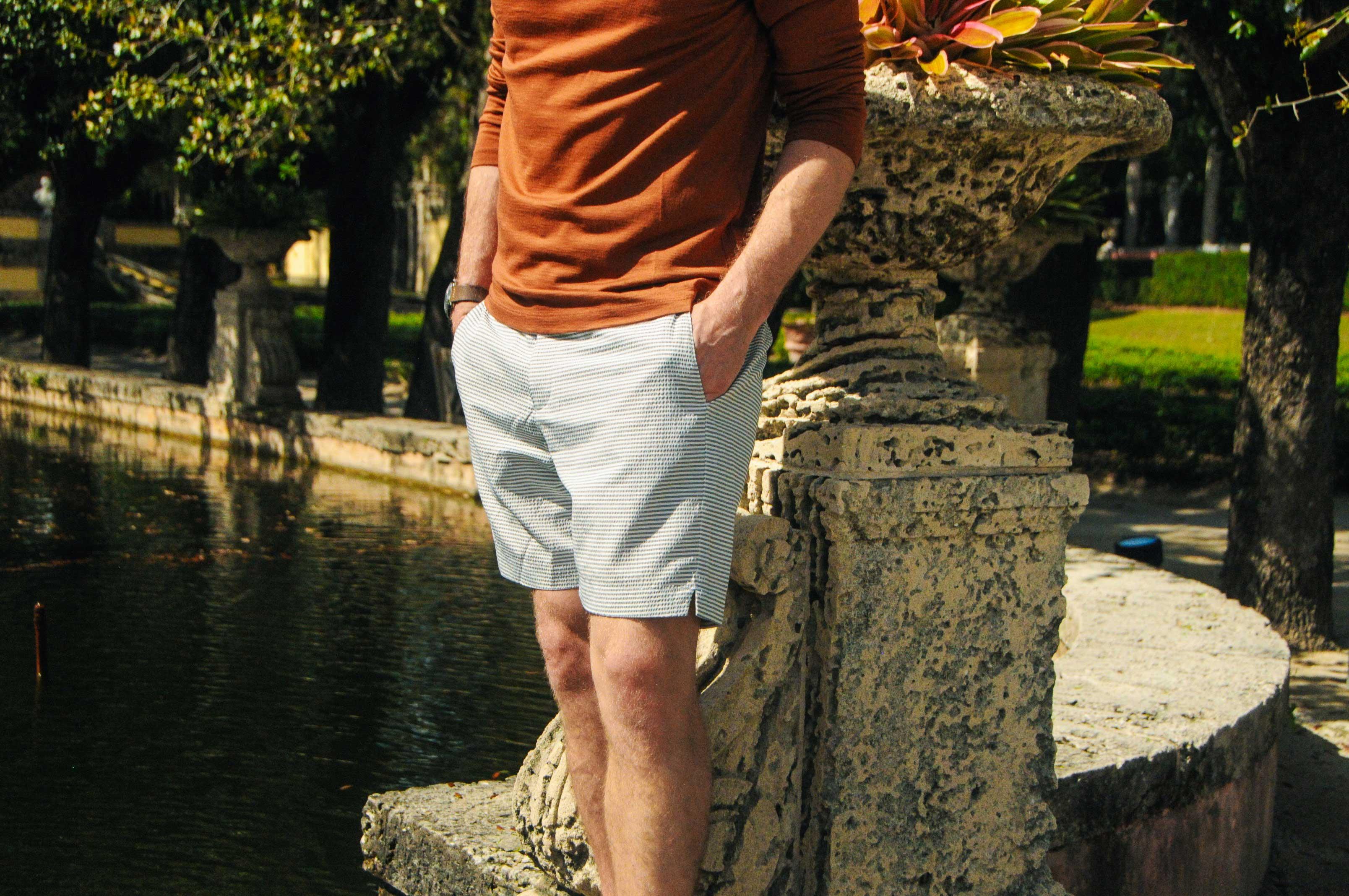 man wearing seersucker shorts and orange cotton tee leaning on pillar
