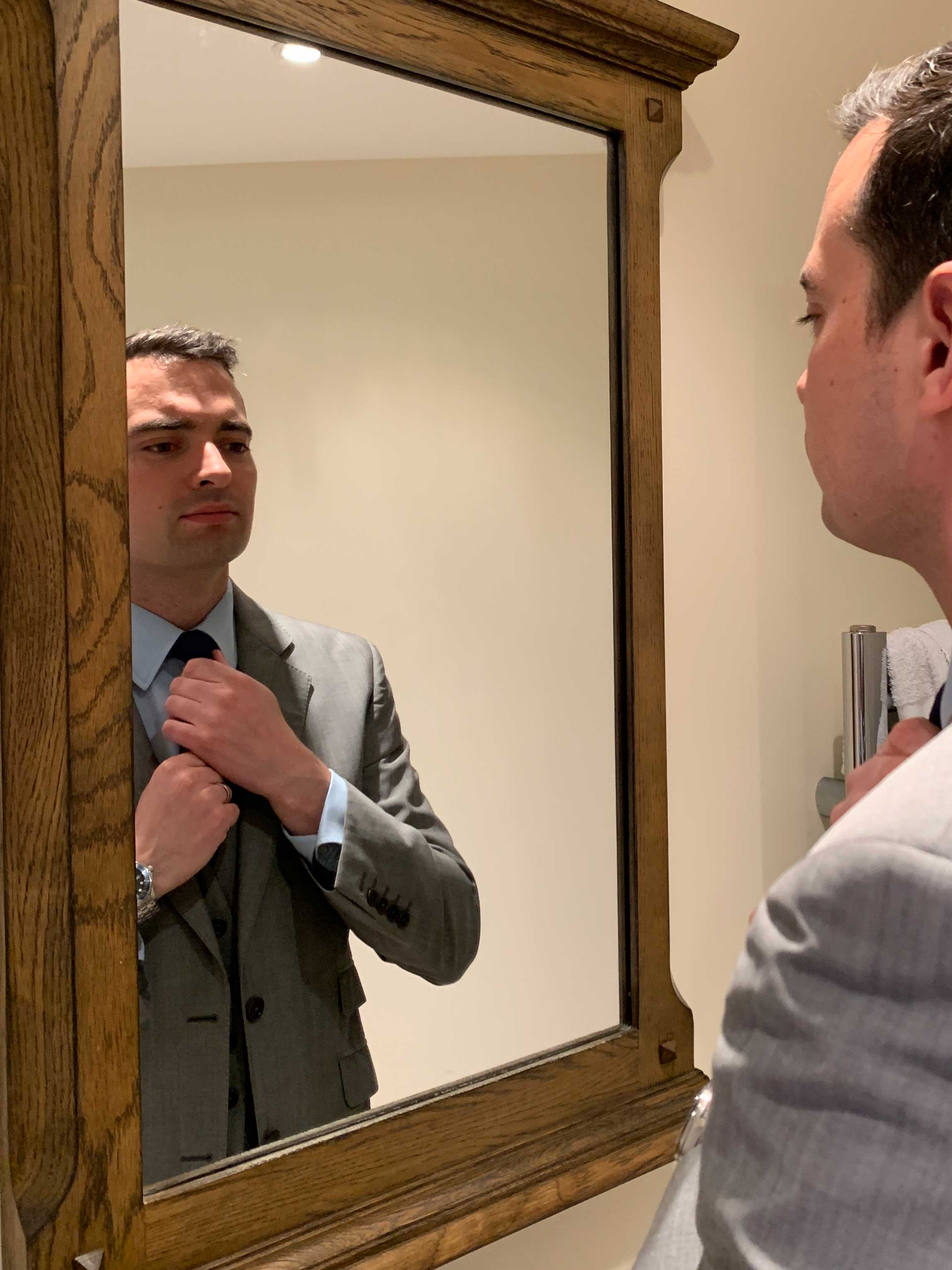 daniel in a suit in the mirror