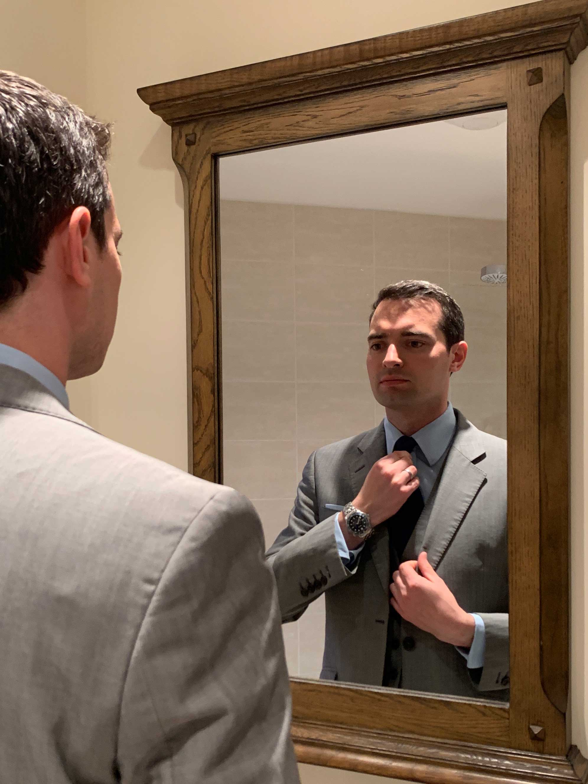 daniel in the mirror in a suit