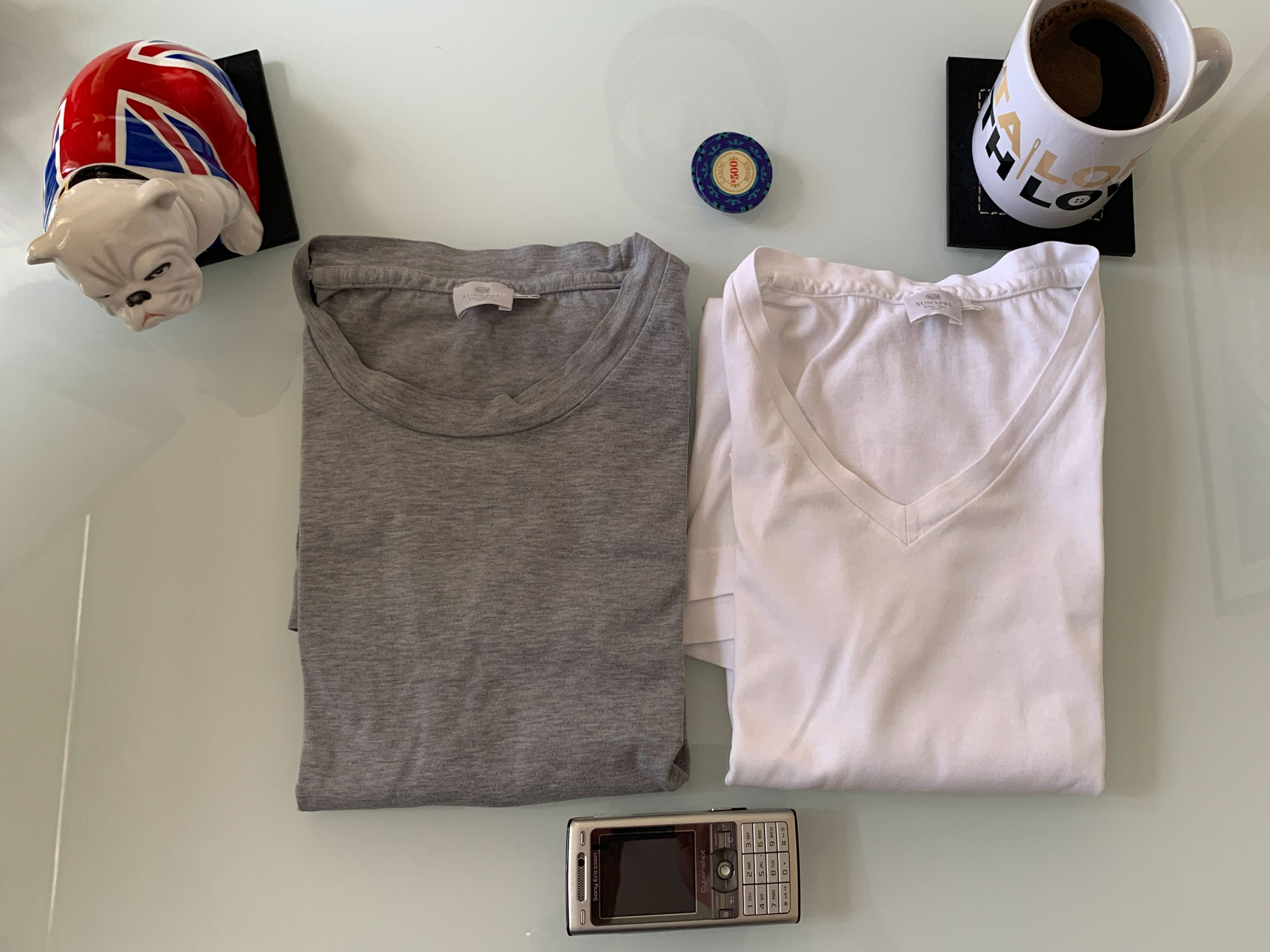 T-Shirts white and grey laid out on a table with props