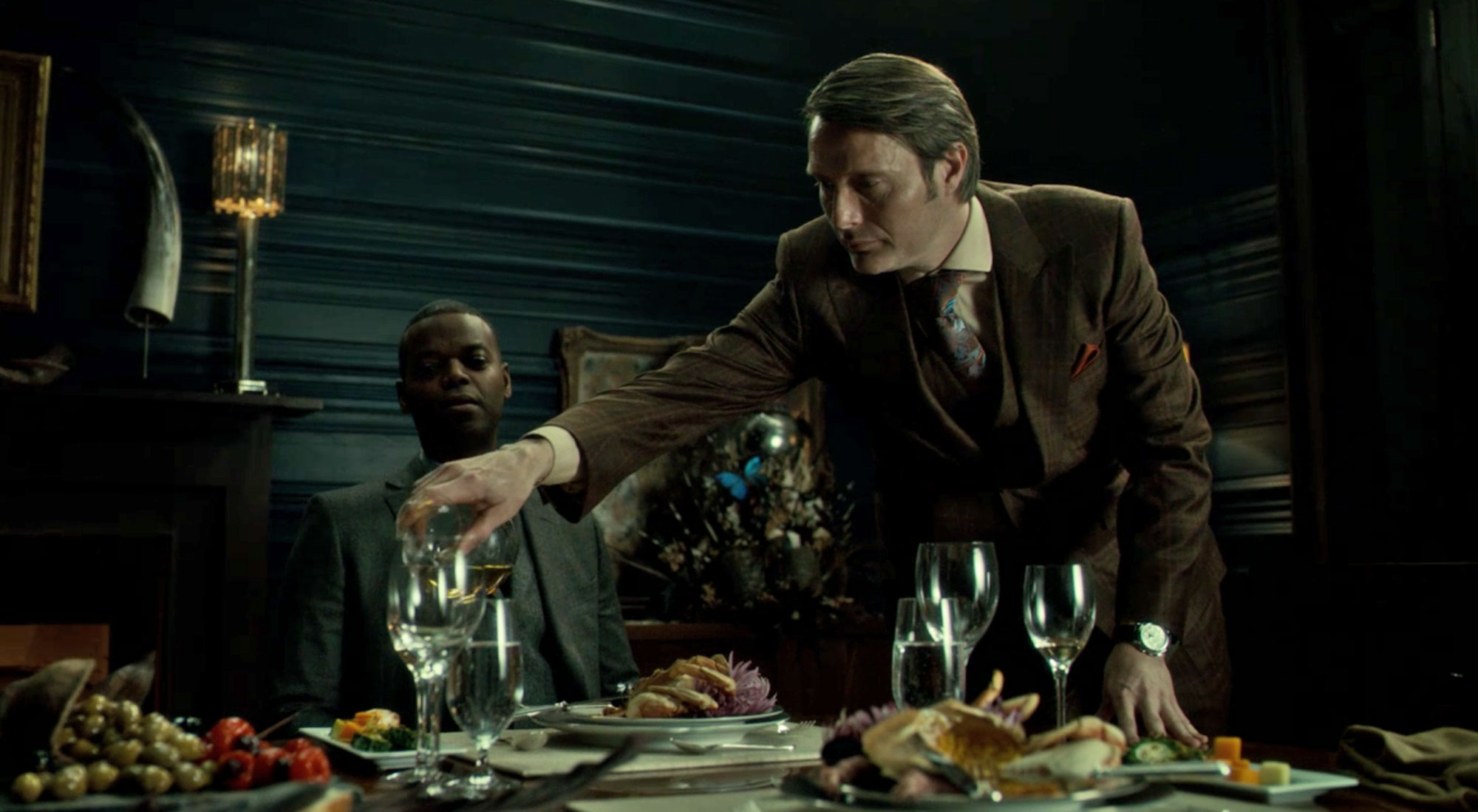 Mads Mikkelsen wearing a three piece costume designed by Christopher Hargadon in Hannibal pouring wine