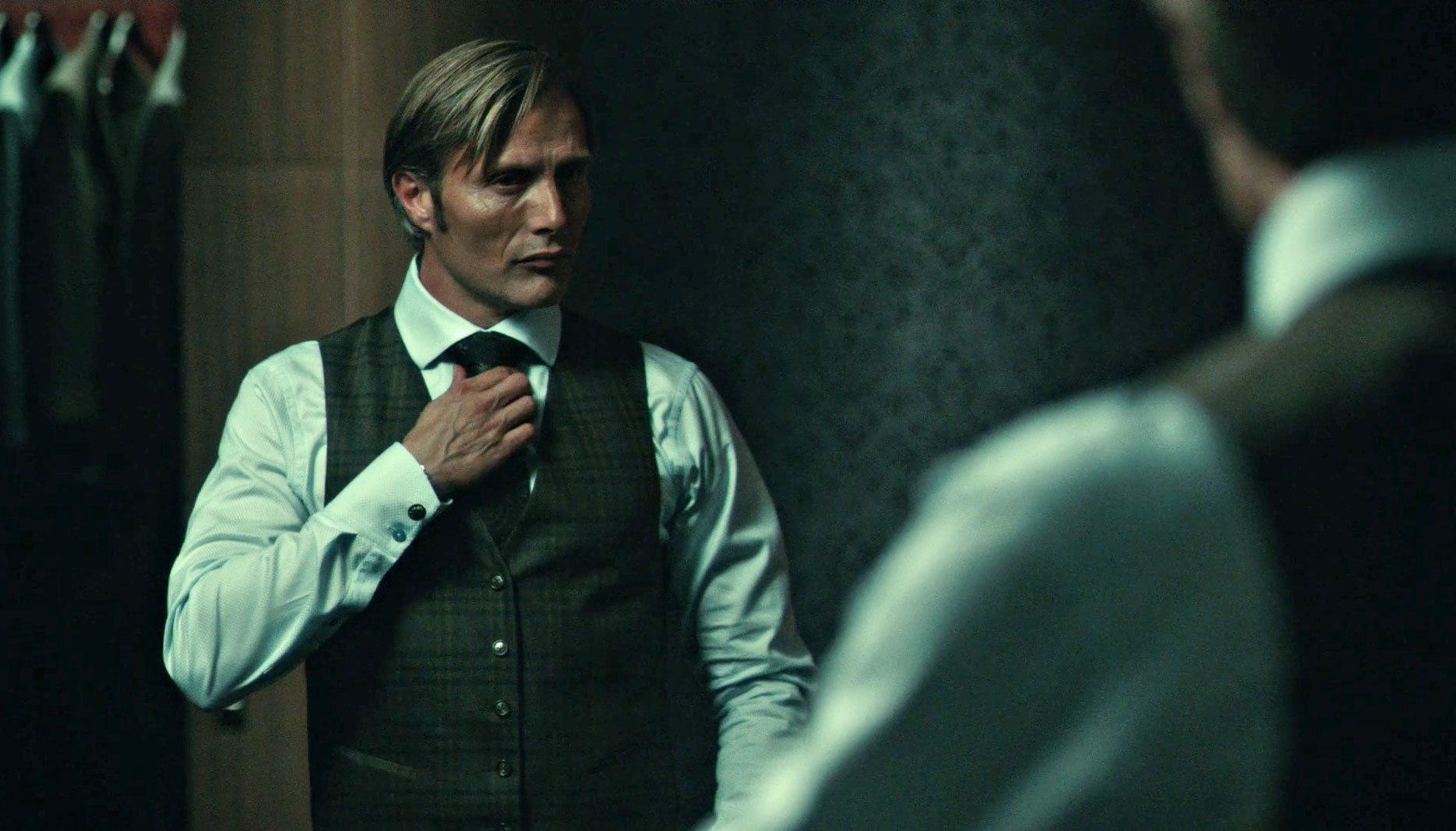 Mads Mikkelsen getting ready in the mirror wearing clothes designed by Christopher Hargadon
