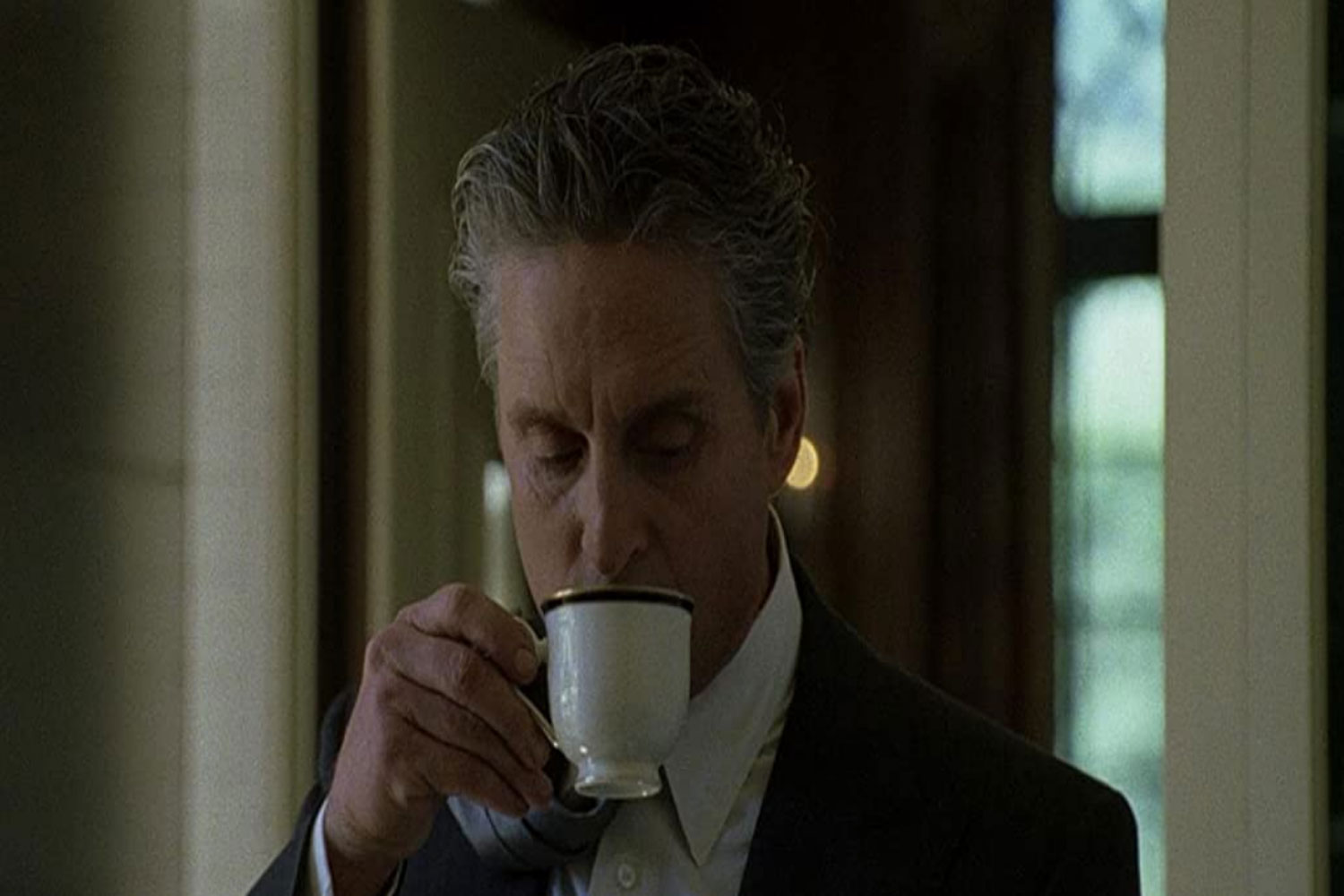 Michael douglas in The Game drinking coffee with his tie over his shoulder